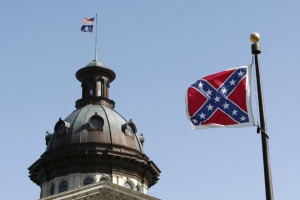 A Confederate flag flies at the base of a confederate memorial in front of the South Carolina State House in Columbia, South Carolina July 4, 2015.  South Carolina lawmakers plan to introduce a resolution on Tuesday to begin a debate on removing the Confederate flag from the State House grounds after the June 17 shooting of nine black churchgoers at a historic black church in Charleston, South Carolina. The man arrested in the shooting, Dylann Roof, is a 21-year-old white man who had posed with a Confederate battle flag in photos posted on a website that displayed a racist manifesto attributed to him.  REUTERS/Tami Chappell